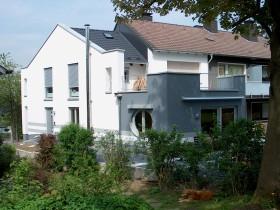 Blick auf Mehrfamilienhaus-Anbau vom Garten aus
