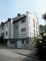 Blick auf Mehrfamilienhaus-Anbau mit Garage von der Strasse aus